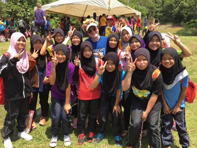 Photo of Cori with school children.