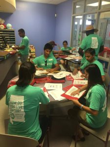 The school volunteers organizing and helping preparing folders for the school's incoming students.